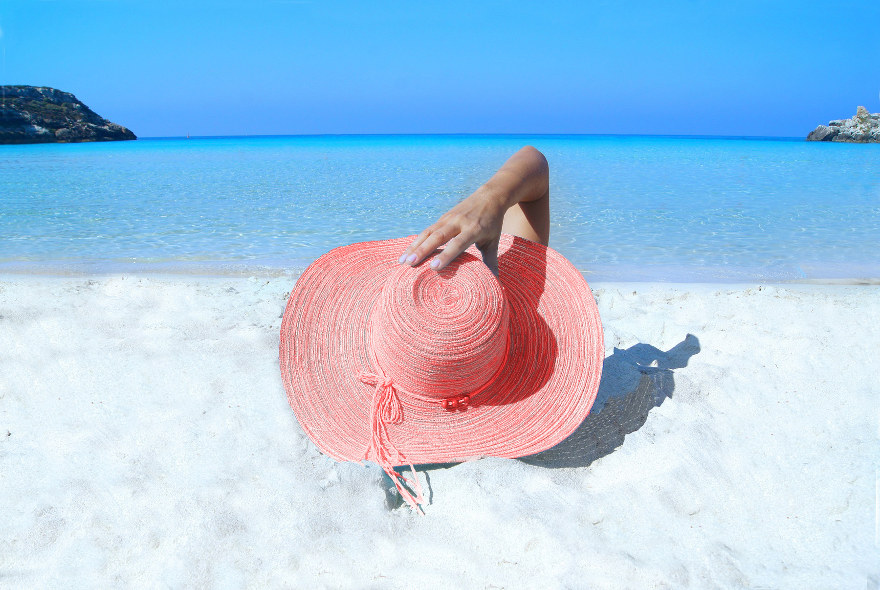 woman on beach with coral hat